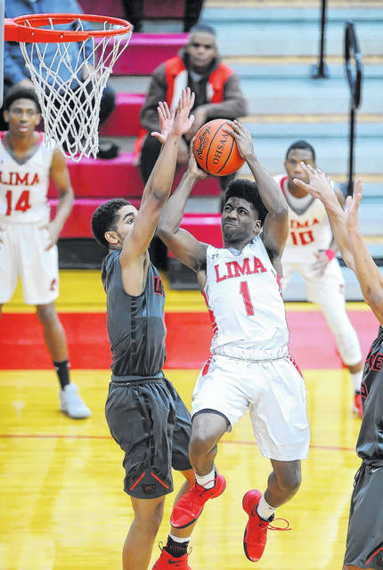 Lima Senior's Bryan Miller Jr. puts up a shot against Wayne's Deshon Parker during Saturday night's Kewpee Holiday Classic championship game at Lima Senior.