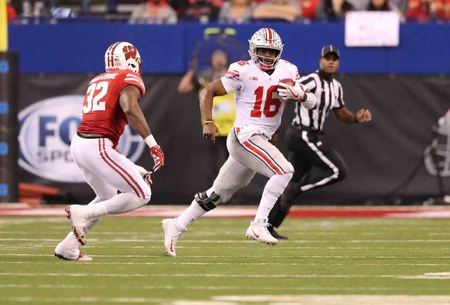 Ohio State quarterback J.T. Barrett scrambles to get away from Wisconsin outside linebacker Leon Jacobs in the first quarter of Sataurday's Big Ten championship game in Indianapolis.
