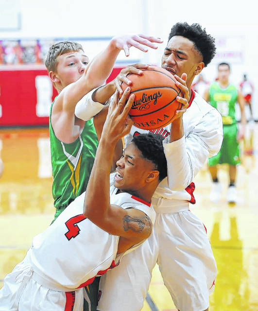 Perry's Chazz Jackson, center, and Malique Cooper grab a rebound against Cory Rawson's Eric Ritter during Tuesday night's game at Perry's Leonard V. Volbert Gymnasium. See more game photos at LimaScores.com.