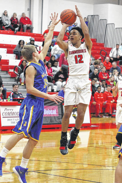 Perry's Jamal Whiteside puts up a shot against Collin Will of Delphos St. John's during Saturday night's game at Perry.
