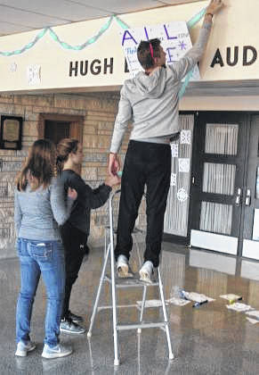 Gabrielle Scott, from left, Rachel Russ and Gabe Williams help decorate the entrance at Shawnee High School with positive messages.