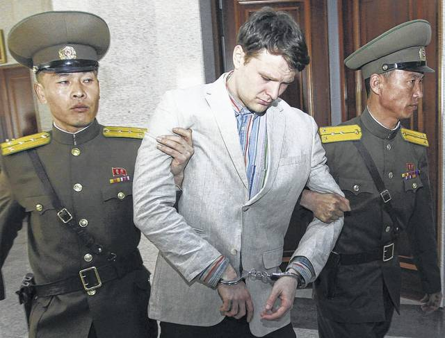 In this March 16, 2016, photo, American student Otto Warmbier, center, is escorted at the Supreme Court in Pyongyang, North Korea. Warmbier, an American college student who was released by North Korea in a coma after almost a year and a half in captivity, died June 19.