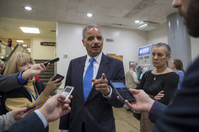 "Former Attorney General Eric Holder takes questions from reporters at the Capitol where he attended the swearing-in of Sen. Doug Jones, D-Ala., in Washington, Wednesday, Jan. 3, 2018. Holder says he is ""deeply disturbed"" that Attorney General Jeff Sessions hasn't spoken out to defend his employees at the Justice Department amid Republican criticism of the FBI. At far right is Holder's wife, Sharon Malone. (AP Photo/J. Scott Applewhite)"