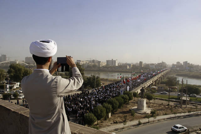 In this photo provided by the Iranian Students' News Agency, a clergyman takes a picture of a pro-government demonstration in the southwestern city of Ahvaz, Iran, Wednesday, Jan. 3, 2018. Tens of thousands of Iranians took part in pro-government demonstrations in several cities across the country on Wednesday, Iranian state media reported, a move apparently seeking to calm nerves after a week of protests and unrest that have killed at least 21 people. (Mohammad Ahangari/ISNA via AP)