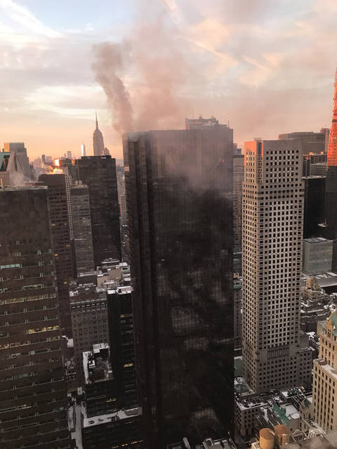 FILE - In this Monday, Jan. 8, 2018 file photo, smoke rises from Trump Tower in New York. The Associated Press has found that stories circulating on the internet that this fire was an assassination attempt on the president are untrue. (Jeff Levi via AP)
