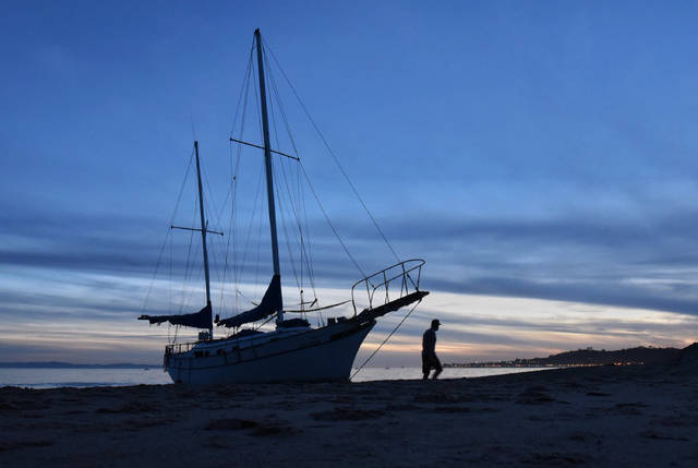 In this Saturday, Jan. 13, 2018 photo provided by the Santa Barbara County Fire Department, a man walks near a sailboat that broke free of its mooring and washed ashore at East Beach in Santa Barbara, Calif., during Tuesday's storm. (Mike Eliason/Santa Barbara County Fire Department via AP)