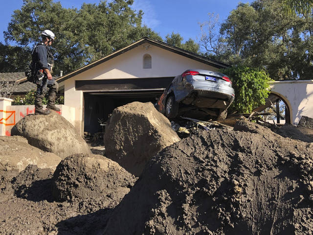 In this Saturday, Jan. 13, 2018 photo provided by the Santa Barbara County Fire Department, Capt. John Pepper, Fresno Fire Department, and Rescue Squad Leader RTF-5 searches homes off East Valley Road in Montecito, Calif. (Mike Eliason/Santa Barbara County Fire Department via AP)