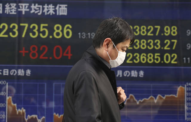 A man walks by an electronic stock board of a securities firm in Tokyo, Monday, Jan. 15, 2018. Asian stock markets edged higher on Monday after Wall Street's strong finish last week. The U.S. dollar weakened against most major currencies, including the Japanese yen. (AP Photo/Koji Sasahara)