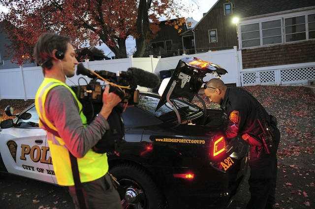 """In this Nov. 3, 2016 photo, a crew from the television program """"Live PD,"""" a reality show by the A&E Network, records an officer from the Bridgeport Police Department while on patrol in Bridgeport, Conn. Some law enforcement agencies, including the Bridgeport Police, have ended their agreements to be on the show after local government leaders concluded the national spotlight on criminal activity overshadowed the positive things happening in their hometowns. (Christian Abraham/Hearst Connecticut Media via AP)"""