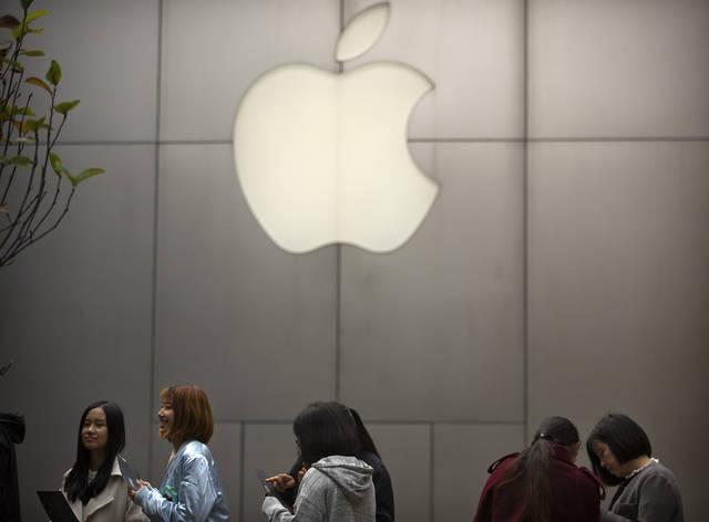 FILE - In this Friday, Oct. 20, 2017, file photo, people stand in line near an Apple Store at an outdoor shopping mall in Beijing, China. On Wednesday, Jan. 17, 2018, Apple announced it is planning to build another corporate campus and hire 20,000 workers during the next five years as part of a $350 billion commitment to the U.S. economy. (AP Photo/Mark Schiefelbein, File)