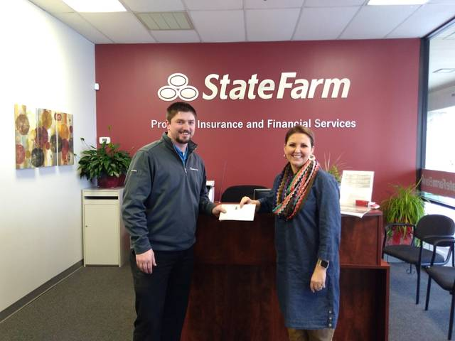 """Steven Slusser, of Van Wert, won Ohio City's Pride 2017 """"Holiday Lights"""" contest for Van Wert County and receives his prize money from Tisha Fast of State Farm."""