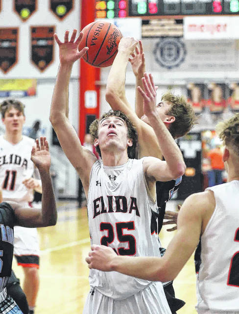 Elida's Skyler Smith and Lima Central Catholic's Brendan Stolly go for a rebound during Saturday night's game at the Elida Fieldhouse.
