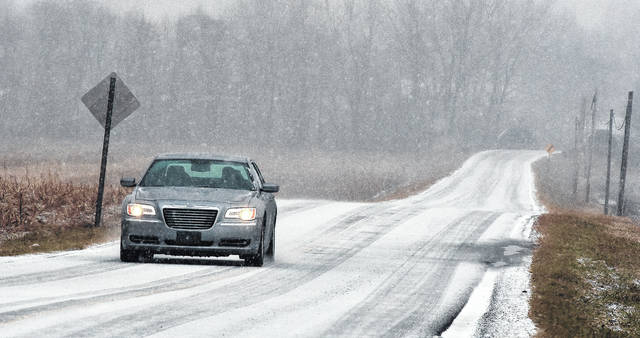 A car travels down North Copus Road covered in ice and snow during Friday's treacherous weather mix.