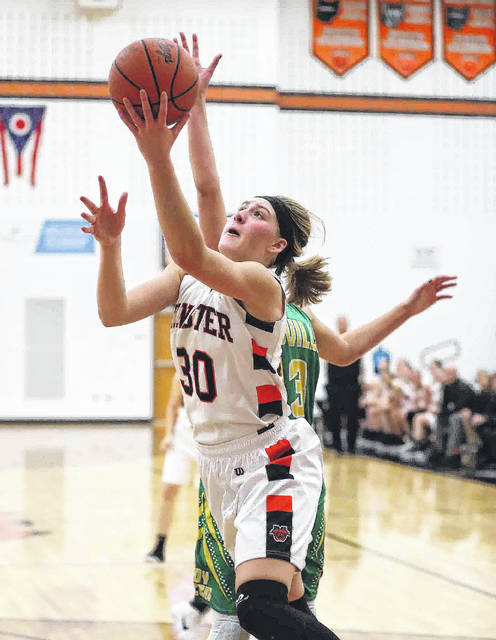 Minster's Courtney Prenger puts up a shot against Ottoville's Bridget Landin during Saturday's game at Minster.