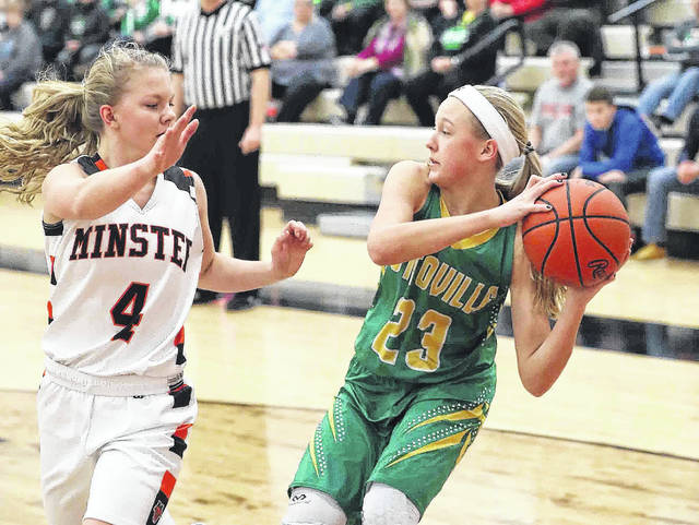 Minster's Ivy Wolf applies pressure against Ottoville's Kasey Knippen during Saturday's game at Minster.