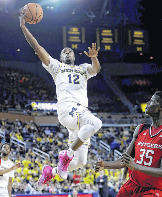 Michigan guard Muhammad-Ali Abdur-Rahkman (12) makes a layup as Rutgers guard Issa Thiam (35) defends during the second half of an NCAA college basketball game, Sunday, Jan. 21,2018, in Ann Arbor, Mich. (AP Photo/Carlos Osorio)