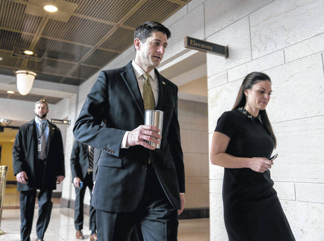 House Speaker Paul Ryan of Wis., center, accompanied by his Press Secretary AshLee Strong, right, walks to the Capitol Building from the Capitol Visitor's Center, Thursday, Jan. 18, 2018, in Washington.