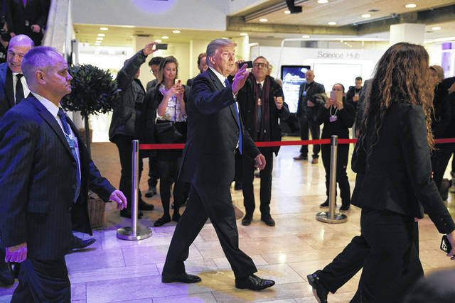 President Donald Trump waves as he walks to a dinner with European business leaders at the World Economic Forum, Thursday, Jan. 25, 2018, in Davos.