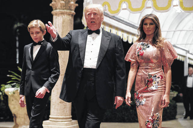 President Donald Trump, first lady Melania Trump, and their son Barron arrive for a New Year's Eve gala at his Mar-a-Lago resort Sunday, Dec. 31, 2017, in Palm Beach, Fla.