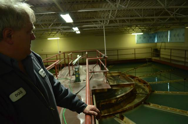 Doug Schoeder, Ottawa Water Treatment Plant Director, explains the process taking place in the water clarification room. Lime and other chemicals in the water collect near the bottom of the chamber and cleaner water flows down the small troughs, around the center and out into the plant to continue treatment. The windows are covered because algae can only bloom if there is a source of UV light in the room, he said.