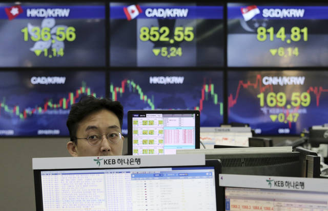 A currency trader works at the foreign exchange dealing room of the KEB Hana Bank headquarters in Seoul, South Korea, Monday, Feb. 19, 2018. Asian markets were higher on Monday following Wall Street gains last week, as market jitters showed signs of easing. Many major markets were closed on holidays. (AP Photo/Ahn Young-joon)