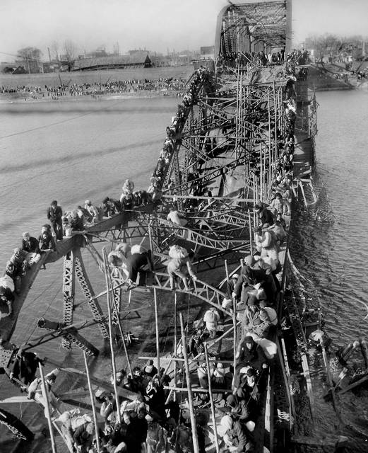 FILE - In this Dec. 4, 1950, file photo, residents from Pyongyang, North Korea, and refugees from other areas crawl perilously over shattered girders of the city's bridge, as they flee south across the Taedong River to escape the advance of Chinese Communist troops. Former Associated Press photographer Max Desfor, whose photo of hundreds of Korean War refugees crawling across a damaged bridge in 1950 helped bring him a Pulitzer Prize, died Monday, Feb. 19, 2018. He was 104. (AP Photo/Max Desfor, File)