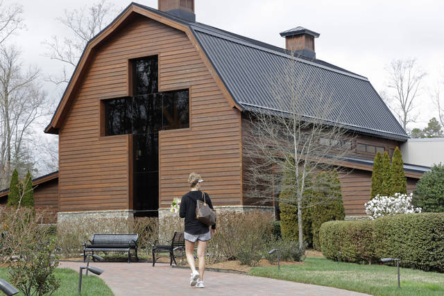 Jo Dockins, of Charlotte, N.C., carries flowers as she visits the Billy Graham Library in Charlotte, N.C., Wednesday, Feb. 21, 2018.  Spokesman Mark DeMoss says Billy Graham, who long suffered from cancer, pneumonia and other ailments, died at his home in North Carolina on Wednesday, Feb. 21, 2018. He was 99. (AP Photo/Chuck Burton)