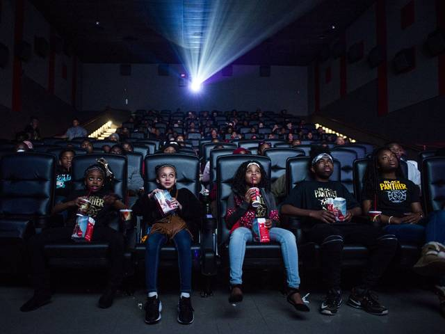 "Mari Copeny, third from left, watches a free screening of the film ""Black Panther"" with more than 150 children after she raised $16,000 to provide free tickets in an entire theater Monday in Flint Township, Mich. As ""Black Panther"" debuts in theaters across the U.S., educators, philanthropist, celebrities and business owners are pulling together their resources to bring children of color to see the film that features a black superhero in a fictional, un-colonized African nation."