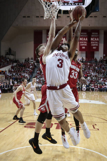 Indiana forward Justin Smith, center, goes to the basket in front of Ohio State center Micah Potter, left, and forward Keita Bates-Diop during the first half of an NCAA college basketball game in Bloomington, Ind., Friday, Feb. 23, 2018. (AP Photo/AJ Mast)