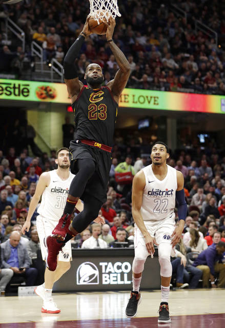 Cleveland Cavaliers' LeBron James (23) drives to the basket against Washington Wizards' Tomas Satoransky (31) and Otto Porter Jr. in the first half of an NBA basketball game, Thursday, Feb. 22, 2018, in Cleveland. (AP Photo/Tony Dejak)