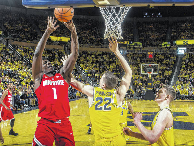 Ohio State forward Jae'Sean Tate (1) attempts a shot while defended by Michigan's Duncan Robinson (22) and Moritz Wagner, right, in the second half of OSU's loss to the Wolverines on Sunday.