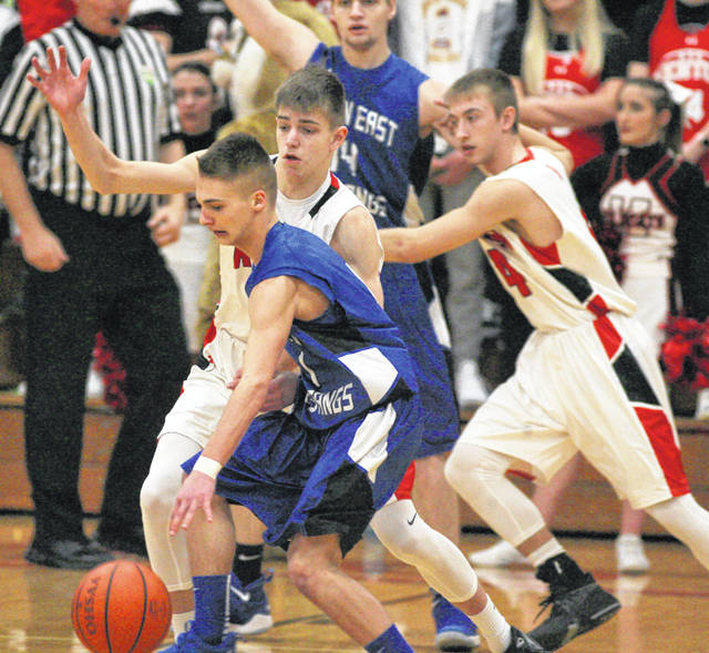 Allen East's Bradden Crumrine tries to shed Kenton defenders during Saturday's night game in Kenton.