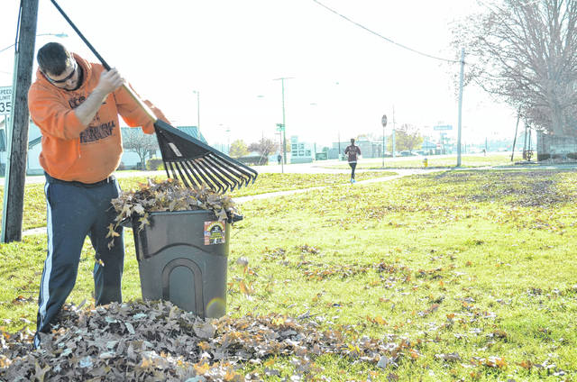 Tavis Kuhlman, of Ottawa, takes advantage of warm weather in December to clean up a yard full of leaves.