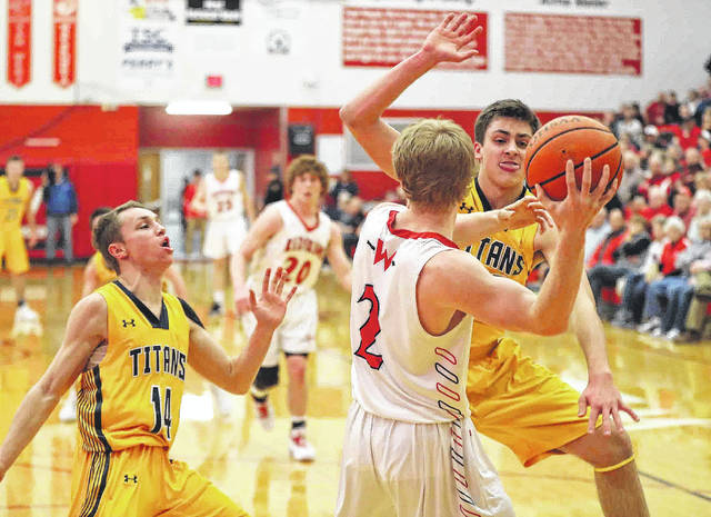 Ottawa-Glandorf's Bryce Schroeder, left, and Ethan White pressure Wapakoneta's Gage Schenk during Friday night's game at Wapakoneta.