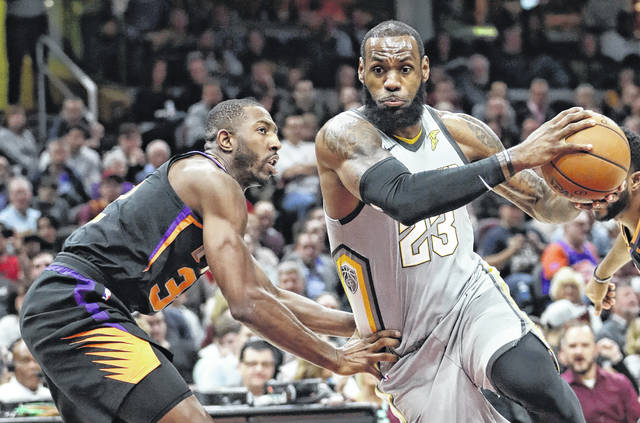 The Cavaliers' LeBron James, right, drives past Phoenix's Davon Reed during Friday night's game in Cleveland.