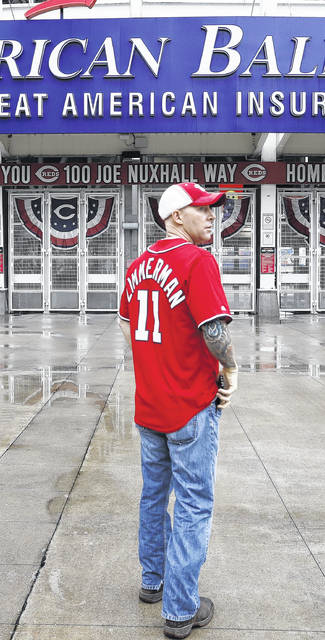 Washington fan Joshua Adam Beach stands Thursday outside the front gates of Great American Ballpark in Cincinnati where the Reds-Nationals game was postponed until today.