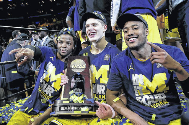 From left, Michigan's Xavier Simpson, a Lima Senior graduate, Moritz Wagner and Muhammad-Ali Abdur-Rahkman celebrate Saturday night after defeating Florida for the West Regional championship.