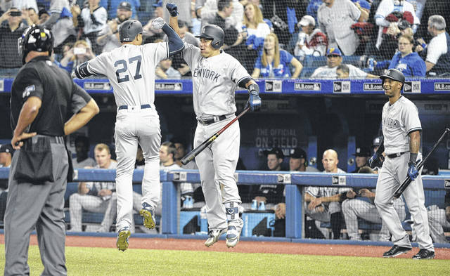 New York Yankees' Giancarlo Stanton (27) celebrates one of his home runs with Gary Sanchez, center, as Aaron Hicks, right, looks on during the ninth inning baseball of Thursday's gameagainst the Blue Jays in Toronto/
