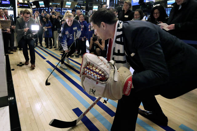 U.S. Olympic gold medal women's hockey team member Jocelyne Lamoureux-Davidson, center, shoots the puck against New York Stock Exchange President Tom Farley on the floor of the New York Stock Exchange, before the team rang the opening bell Tuesday, March 6, 2018. (AP Photo/Richard Drew)