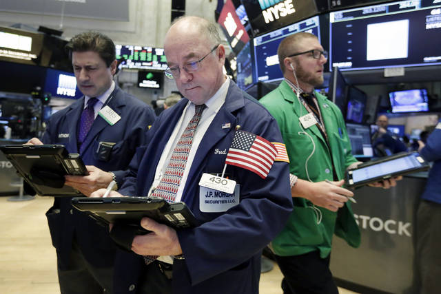 Frederick Reimer, center, works with fellow traders on the floor of the New York Stock Exchange, Tuesday, March 6, 2018. U.S. stocks are little changed Tuesday as banks and big dividend payers decline while technology companies rise. (AP Photo/Richard Drew)