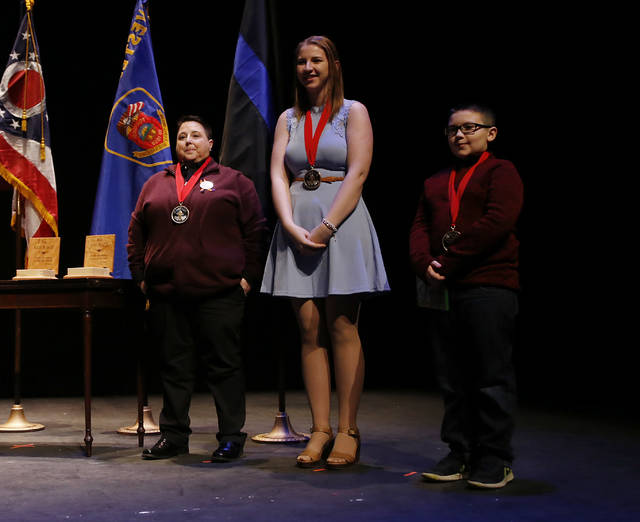 Governor's Courage Award Recipients Chris Hole, left, Nina Schubert and Mikah Frye stand on stage during the Ohio State of the State address in the Fritsche Theater at Otterbein University in Westerville, Ohio, Tuesday, March 6, 2018. (AP Photo/Paul Vernon)
