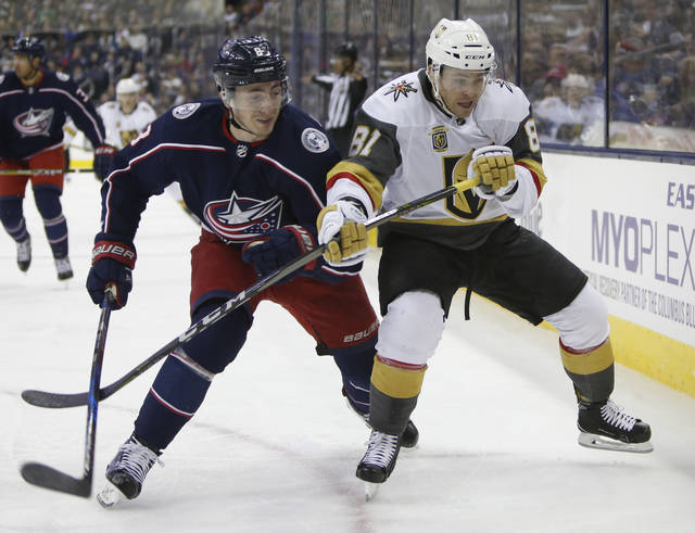 Columbus Blue Jackets' Zach Werenski, left, and Las Vegas Golden Knights' Jonathan Marchessault fight for position during the first period of an NHL hockey game Tuesday, March 6, 2018, in Columbus, Ohio. (AP Photo/Jay LaPrete)