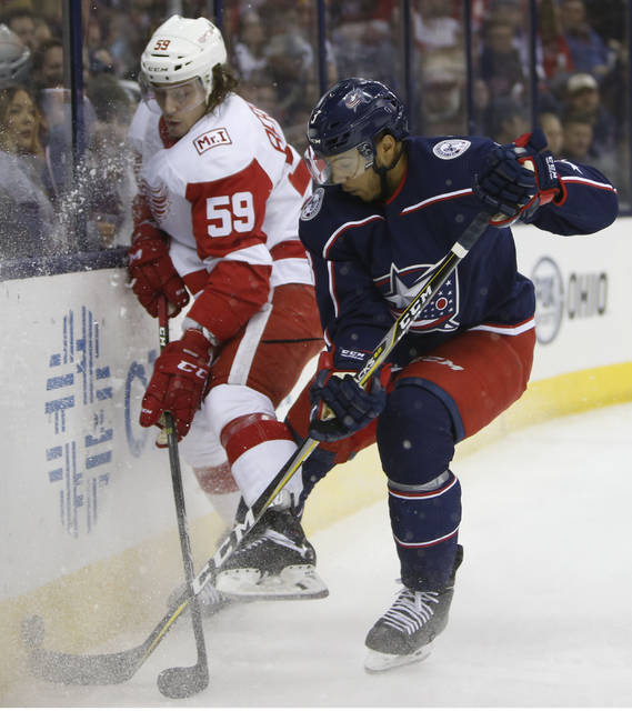 Detroit Red Wings' Tyler Bertuzzi, left, and Columbus Blue Jackets' Seth Jones fight for the puck during the third period of an NHL hockey game Friday, March 9, 2018, in Columbus, Ohio. (AP Photo/Jay LaPrete)