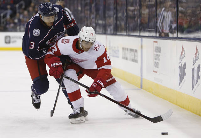 Detroit Red Wings' Andreas Athanasiou, right, carries the puck upice as Columbus Blue Jackets' Seth Jones defends during the third period of an NHL hockey game Friday, March 9, 2018, in Columbus, Ohio. (AP Photo/Jay LaPrete)
