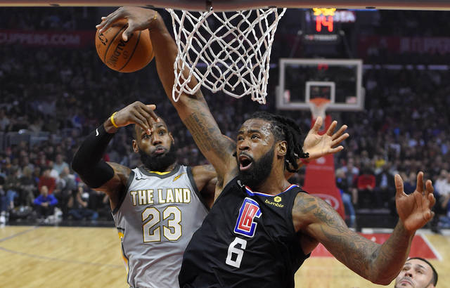 Los Angeles Clippers center DeAndre Jordan tries to get control of the ball after his shot was blocked by Cleveland Cavaliers forward LeBron James, rear, during the first half of an NBA basketball game, Friday, March 9, 2018, in Los Angeles. (AP Photo/Mark J. Terrill)