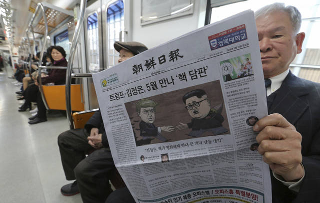 A passenger reads a newspaper with headline of a planned summit meeting between North Korean leader Kim Jong Un and U.S. President Donald Trump, left, at subway train in Seoul, South Korea, Saturday, March 10, 2018. The White House tried to swat away criticism Friday that the U.S. is getting nothing in exchange for agreeing to a historic face-to-face summit between President Donald Trump and North Korean leader Kim Jong Un. (AP Photo/Ahn Young-joon)