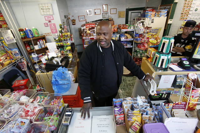 "FILE - In this Feb. 26, 2018, file photo, Carl Lewis in his market in Rankin, Pa. About half of Lewis' customers pay with benefits from the federal Supplemental Nutrition Assistance Program, so the government's proposal to replace the debit card-type program with a pre-assembled box of shelf-stable goods delivered to recipients worries him and other grocery operators in poor areas. Food stamp administrators across the country are expressing reservations about ""America's Harvest Box,"" pitched by Agriculture Department officials as a way to cut costs and improve efficiency. The government is proposing to replace the debit card-type program with a pre-assembled box of shelf-stable goods delivered to recipients. (AP Photo/Gene J. Puskar, File)"