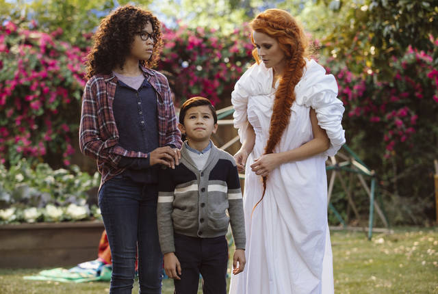 "This image released by Disney shows Storm Reid, from left, Deric McCabe and Reese Witherspoon in a scene from ""A Wrinkle In Time."" (Atsushi Nishijima/Disney via AP)"