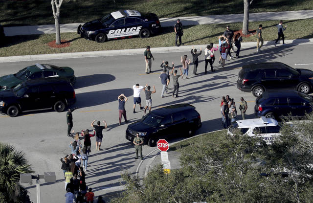 FILE - In this Feb. 14, 2018 file photo, students hold their hands in the air as they are evacuated by police from Marjory Stoneman Douglas High School in Parkland, Fla., after a shooter opened fire on the campus. Emergency calls from parents and students during the Florida high school massacre show 911 operators at first trying to grasp the enormity of the emergency and then calmly trying to gather information to assist arriving law enforcement officers. The officers arrive to find chaos as delays allowed the shooter to flee. (Mike Stocker/South Florida Sun-Sentinel via AP, File)