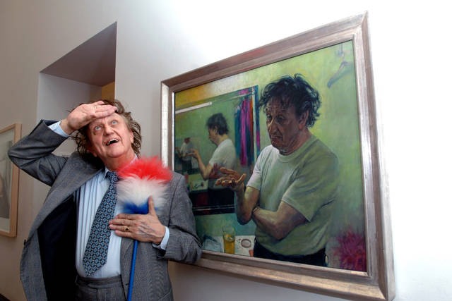 FILE - In this Aug. 17, 2005 file photo, comedian Ken Dodd poses with a new oil on canvas portrait of himself entitled 'Ken Dodd. Entertainer' by Wiltshire artist David Cobley. British comedian Ken Dodd, whose seven-decade career stretched from the music-hall era to the age of social media, has died. He was 90. Publicist Robert Holmes says Dodd died Sunday, March 11, 2018 at his Liverpool home, the same house where he was born in 1927. (Fiona Hanson/PA via AP, File)